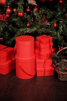 Fundo de celebração de natal ou ano novo de presentes caixas de presente vermelhas e ramos de abeto. os presentes de ano novo ficam embaixo da árvore de natal com brinquedos. plano de fundo para o site. copiar espaço, texto local