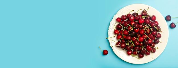 Fundo de cereja. cereja doce suculenta vermelha em um prato branco sobre um fundo azul claro. bagas suculentas frescas de verão e conceito de comida.