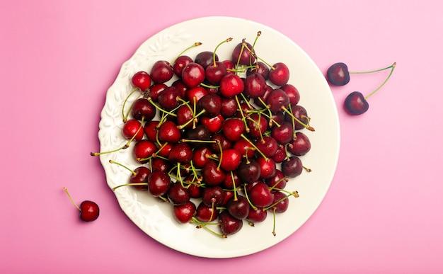 Fundo de cereja. cereja doce suculenta vermelha em um prato branco sobre um fundo rosa claro. bagas suculentas frescas de verão e conceito de comida. foto de alta qualidade