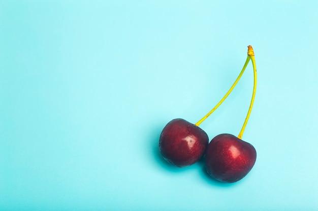 Fundo de cereja. cereja doce suculenta vermelha sobre um fundo azul claro. bagas suculentas frescas de verão e conceito de comida. foto de alta qualidade