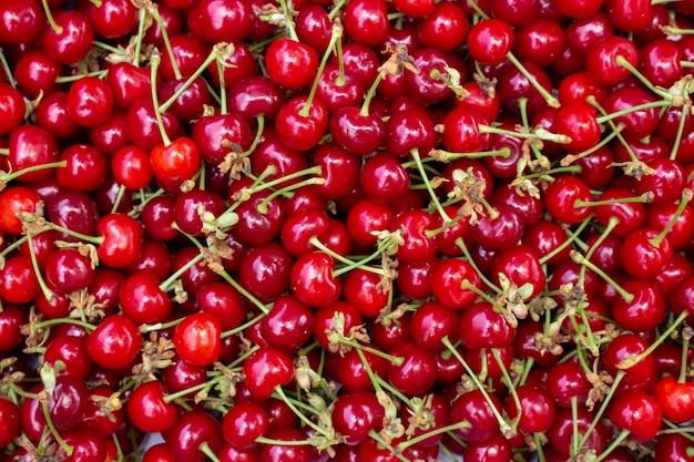 Fundo de cerejas vermelhas com caudas. bagas uniformemente espaçadas, vista de cima.