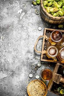Fundo de cerveja. cerveja fresca com ingredientes na mesa rústica.