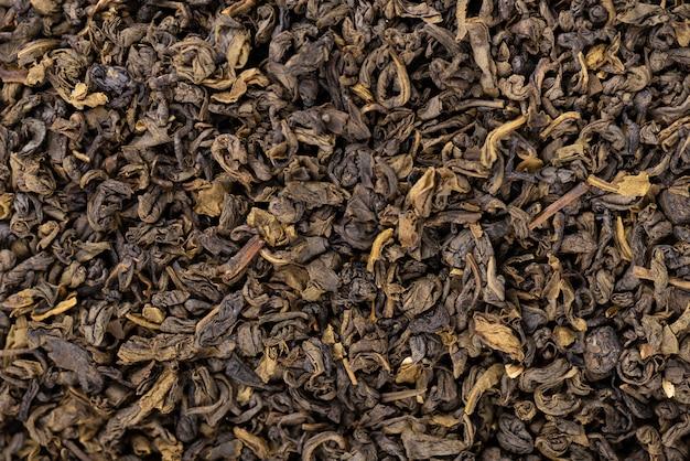 Fundo de chá verde. chá seco verde aromático, fim acima.