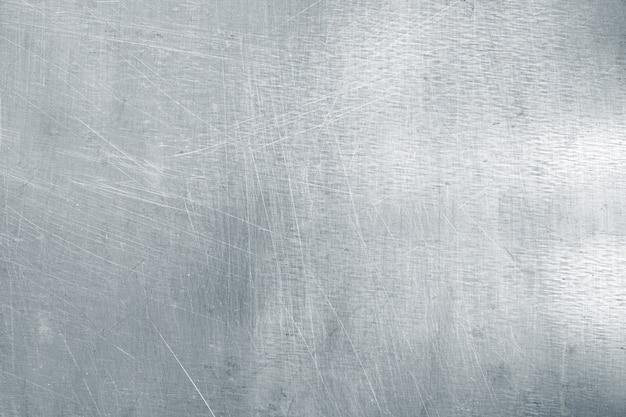 Fundo de chapa de aço desgastado, textura de metal leve com arranhões e amassados