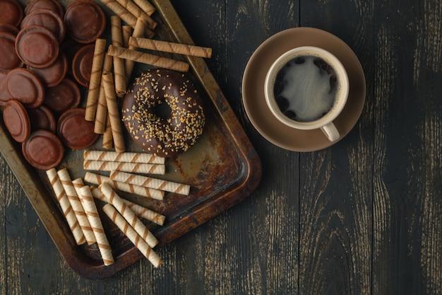 Fundo de chocolates. chocolate. xícara de chocolate quente, limão, nozes e variedade de chocolates finos no escuro e chocolate ao leite na mesa de madeira escura