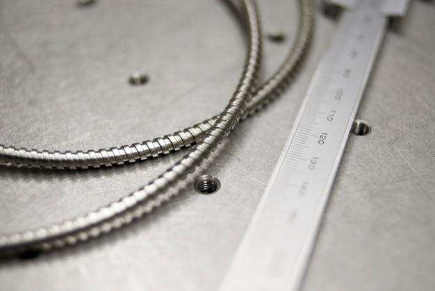Fundo de ciência óptica, escala de compasso de calibre mecânico com macro de fibra na mesa de aço inoxidável; foco seletivo no centro