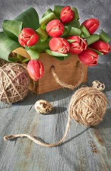 Fundo de comemoração de primavera: monte de tulipas vermelhas, decorações de primavera e ovos pintados em madeira rústica cinza