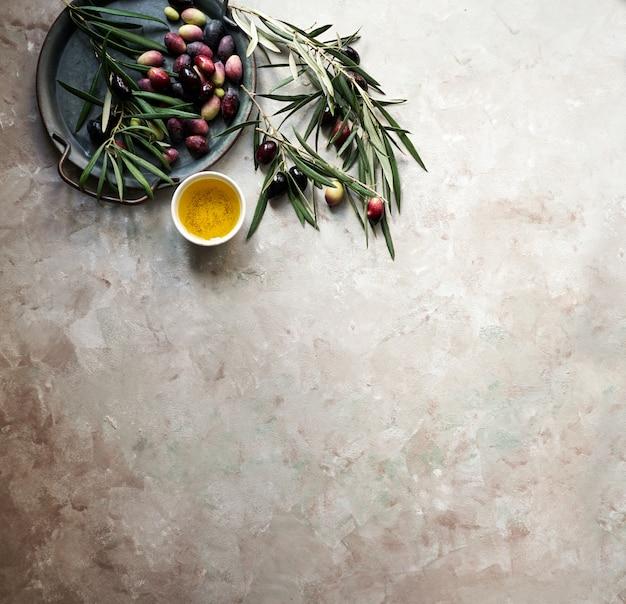 Fundo de comida com galho de oliveira, guardanapo e prato, talheres de faca e garfo, azeite