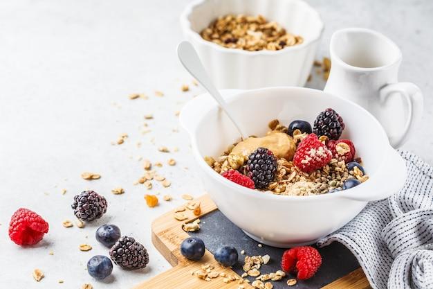 Fundo de comida de café da manhã. granola com sementes de cânhamo, pó de maca, manteiga de amendoim e frutas na mesa branca.