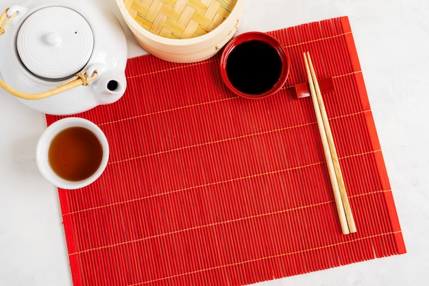Fundo de comida de chá asiático. bule e xícara com pauzinhos na esteira de bambu vermelho sobre o fundo de pedra cinza. maquete para o menu.