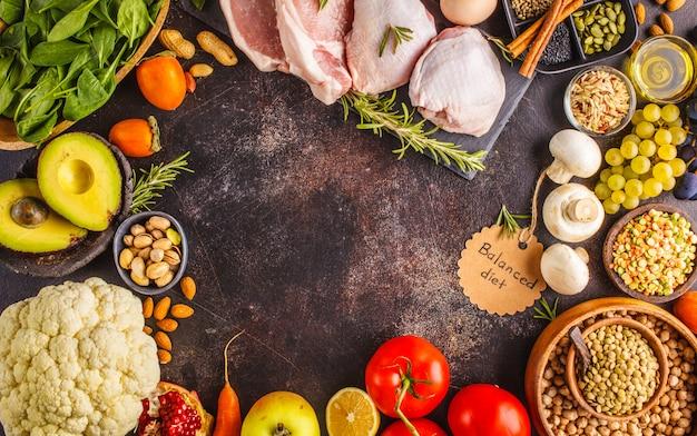 Fundo de comida de dieta equilibrada. ingredientes saudáveis em um fundo escuro, vista superior.
