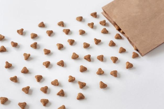 Fundo de comida de gato seca e embalagens de papel. cuide de gatos domésticos.