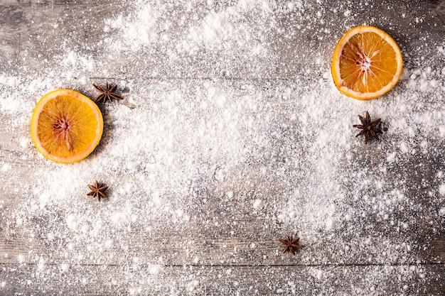 Fundo de comida de natal com laranjas, anis estrelado e farinha