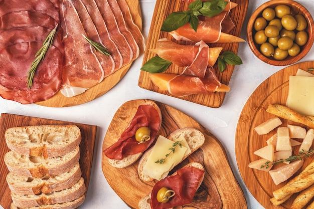 Fundo de comida italiana com presunto, queijo, azeitonas, pão e vinho