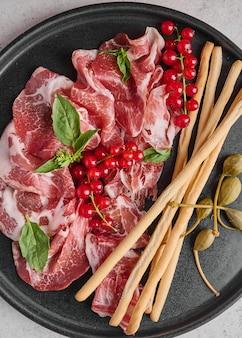 Fundo de comida presunto coppa di parma com manjericão grissini, alcaparras e groselha em