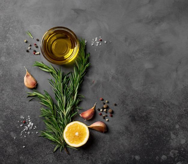 Fundo de comida preto com azeite, alecrim, limão e especiarias. vista superior, cópia do espaço