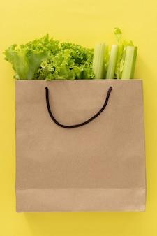 Fundo de comida saudável de entrega. comida vegetariana vegan em vegetais de saco de papel em fundo amarelo. supermercado de comida de compras de supermercado e conceito de alimentação limpa. vista superior. local para texto.