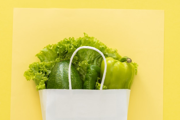 Fundo de comida saudável de entrega. comida vegetariana vegana em vegetais de saco de papel branco sobre fundo amarelo. supermercado de comida de compras de supermercado e conceito de alimentação limpa. vista superior.