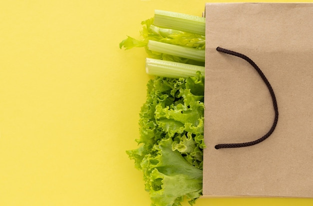 Fundo de comida saudável de entrega. comida vegetariana vegana em vegetais de saco de papel em fundo amarelo. supermercado de comida de compras de supermercado e conceito de alimentação limpa. vista superior.