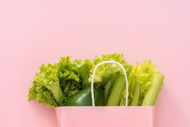 Fundo de comida saudável de entrega. comida vegetariana vegana em vegetais de saco de papel em fundo rosa. supermercado de comida de compras de supermercado e conceito de alimentação limpa. vista superior.