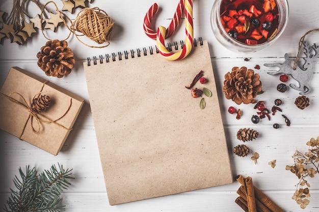 Fundo de composição de natal. árvore de natal, cones, brinquedos e embalagem de presente em fundo branco de madeira.