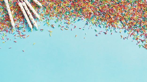 Fundo de conceito de aniversário e festa com confete e velas em azul, vista superior, espaço de cópia, banner