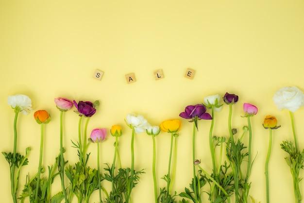Fundo de conceito flatlay de primavera com flores e palavra de madeira de venda
