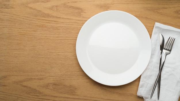 Fundo de configuração de mesa, prato de cerâmica simulado, garfo e faca de mesa em guardanapo branco, vista de cima, prato de cerâmica vazio