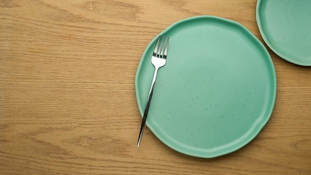Fundo de configuração de mesa, simulação de pratos de cerâmica, garfo e espaço de cópia na mesa de madeira, vista superior, pratos limpos