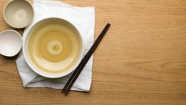 Fundo de configuração de mesa, simulação de tigelas de cerâmica, toalha de mesa e pauzinhos na mesa de madeira, espaço de cópia