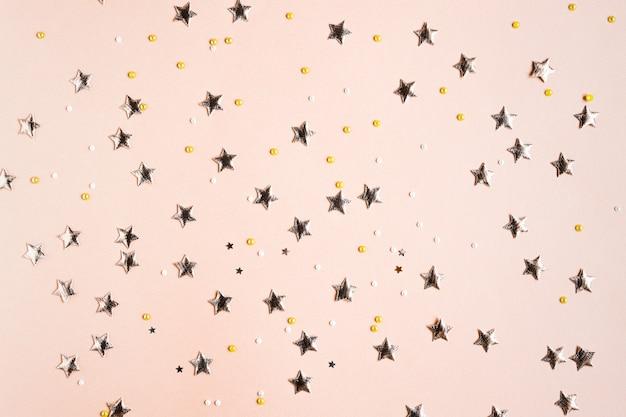 Fundo de cor sólida bege festivo com estrelas douradas e lantejoulas lantejoulas e decorações