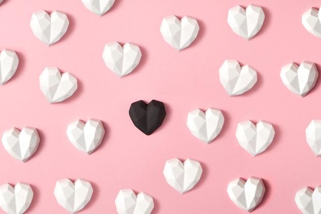 Fundo de corações brancos de gesso e um é preto