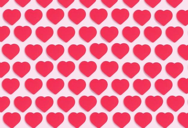 Fundo de corações. padrão de ornamento colorido de recorte corações vermelhos em um fundo rosa. amor, romance, papel de parede, conceito mínimo de cartão postal