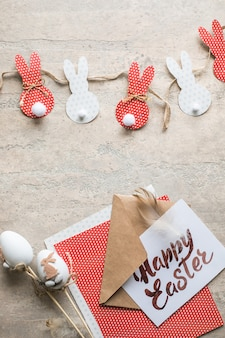 Fundo de corte de papel de decoração de coelhinho da páscoa. guirlanda de artesanato de férias diy de coelhos coloridos e ferramentas de artesanato. vista superior com espaço de cópia