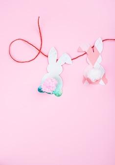 Fundo de corte de papel de decoração de coelhinho da páscoa. guirlanda de artesanato de férias diy de coelhos coloridos e ferramentas de artesanato.