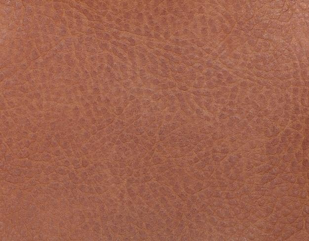 Fundo de couro marrom claro de um material têxtil. tecido com textura natural.