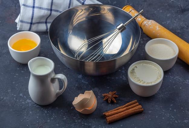 Fundo de cozimento. bacia de metal vazia entre ingredientes e utensílios para cozinhar o bolo na mesa escura. conceito de comida.