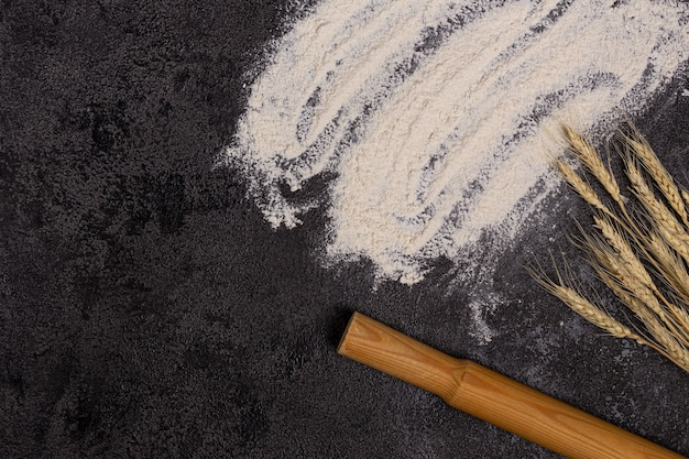 Fundo de cozimento com espaço livre para o seu texto. farinha em uma tigela, ovos e trigo em uma mesa preta