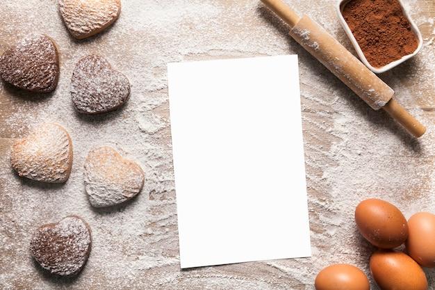 Fundo de cozimento com folha de papel em branco para a receita ou menu, biscoitos em forma de coração, ovos, farinha e rolo.