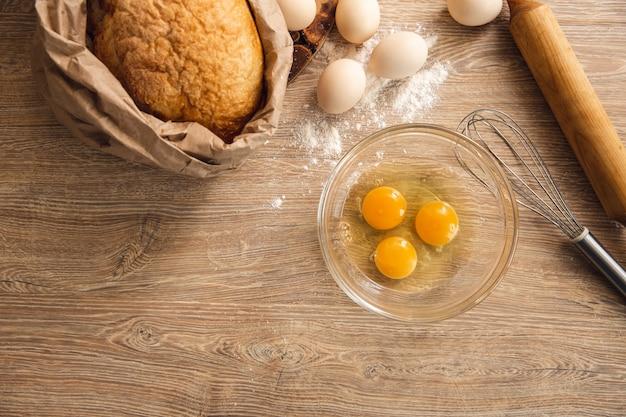 Fundo de cozimento com ovos no prato, pão e utensílio de cozinha