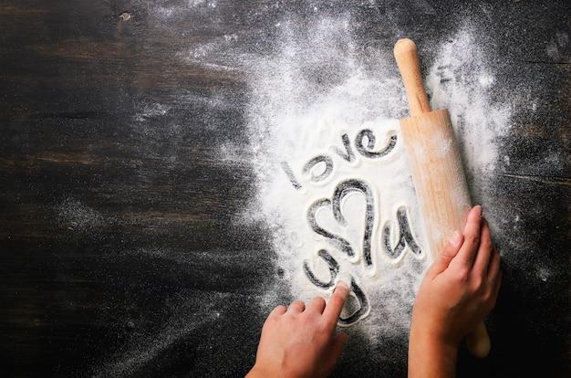 Fundo de cozimento coração de farinha e rolo na mesa escura