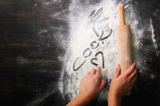 Fundo de cozimento coração de farinha, texto cook and rolling pin na mesa escura
