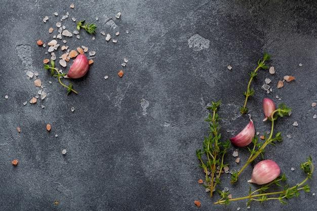 Fundo de cozimento de alimentos. ervas de especiarias e alho na mesa de ardósia preta. vista superior de ingredientes alimentares.