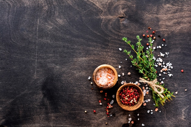 Fundo de cozimento de alimentos. ervas frescas monte tomilho e condimentos na velha mesa de madeira preta. tomilho, sal marinho e pimenta. vista superior de ingredientes alimentares.