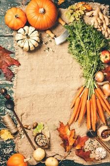 Fundo de cozimento de alimentos saudáveis. cenouras frescas, cebolas, abóboras, gengibre e especiarias em madeira rústica, vista de cima, espaço de cópia