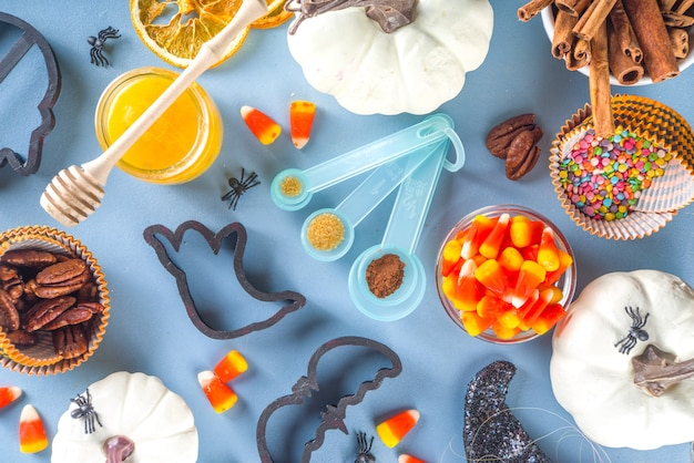 Fundo de cozimento de biscoitos de gengibre de halloween. conceito de cozimento do feriado de outono, ingredientes, especiarias, cortadores de biscoitos de símbolo de halloween - abóbora, fantasma, morcego, chapéu de bruxa, vista de cima, espaço de cópia de mesa azul