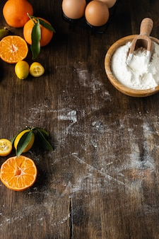 Fundo de cozimento de natal caseiro, mesa de madeira com farinha, ovos e tangerinas