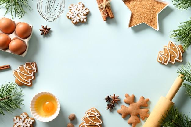 Fundo de cozimento de natal com biscoitos e ingredientes sobre fundo azul. copie o espaço. vista de cima.