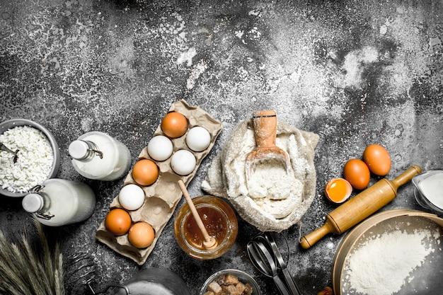 Fundo de cozimento. ingredientes e ferramentas para preparação de massa. sobre um fundo rústico.