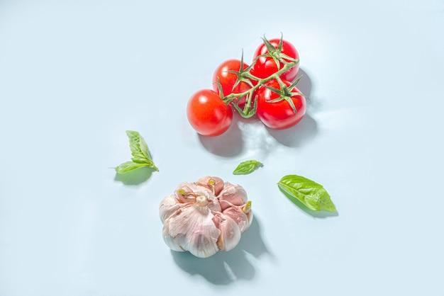 Fundo de cozinha de comida mediterrânea, tomates frescos, manjericão, azeite e alho no fundo azul